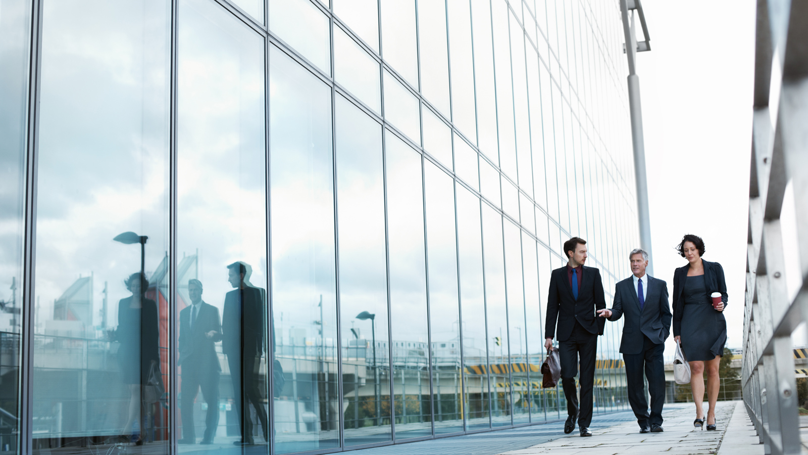 3 executive people walking together by the side of a build having glass walls.