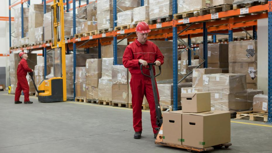 Man in a warehouse carrying out boxes