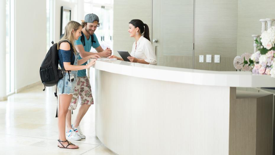 Couple checking in the reception of a hotel/hostel.
