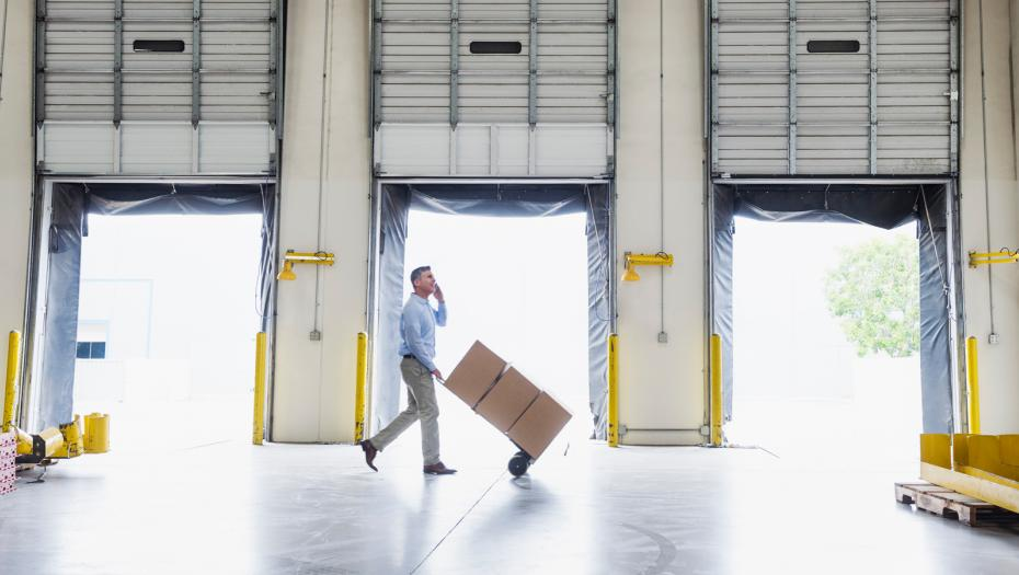 Man carrying out boxes inside a warehouse.