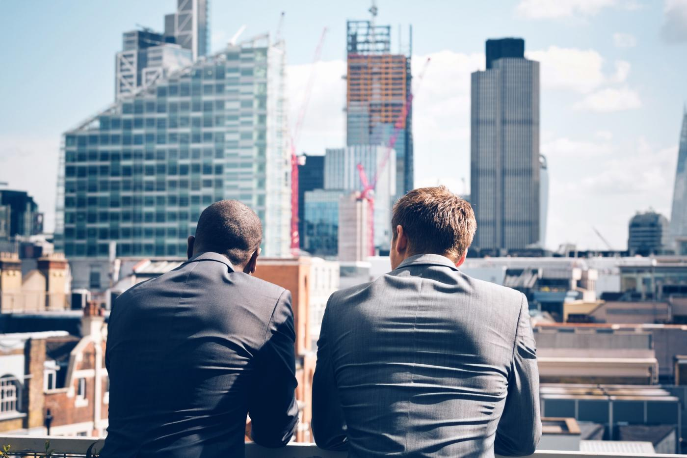 Two business men in balcony staring at the city.