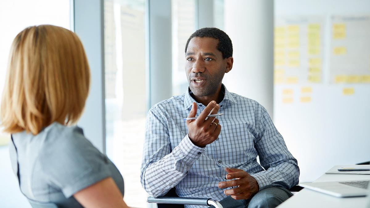 Man talking to woman in a meeting room.